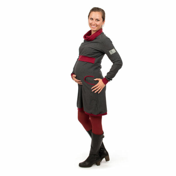 Maternity sweater dress and nursing dress NEELE in anthracite bordeaux - pregnant model with hand under baby bump - full side view