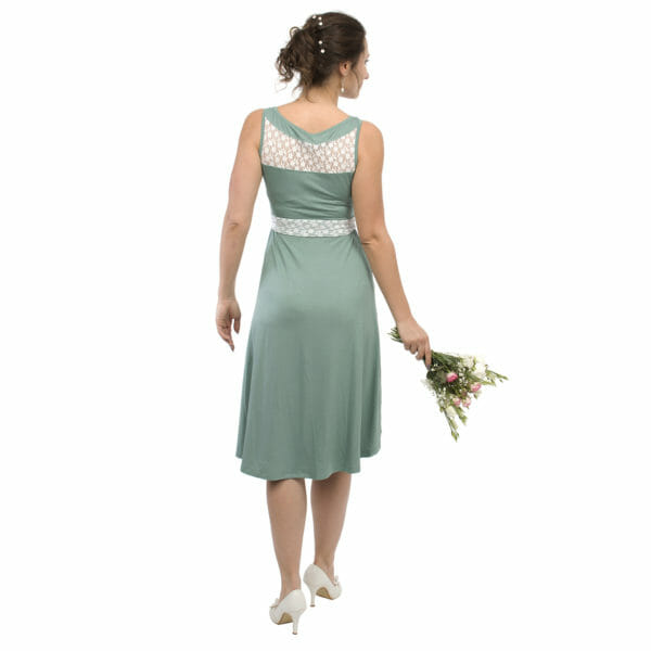 Maternity and nursing cocktail dress ALMA in mint with white lace - model wears dress and has bunch of flowers in right hand - view from back