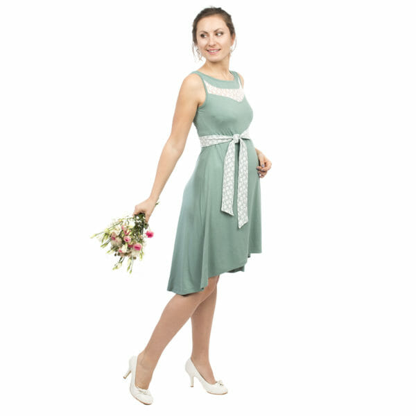 Maternity and nursing cocktail dress ALMA in mint with white lace - pregnant model wears dress and has bunch of flowers in right hand and is looking back