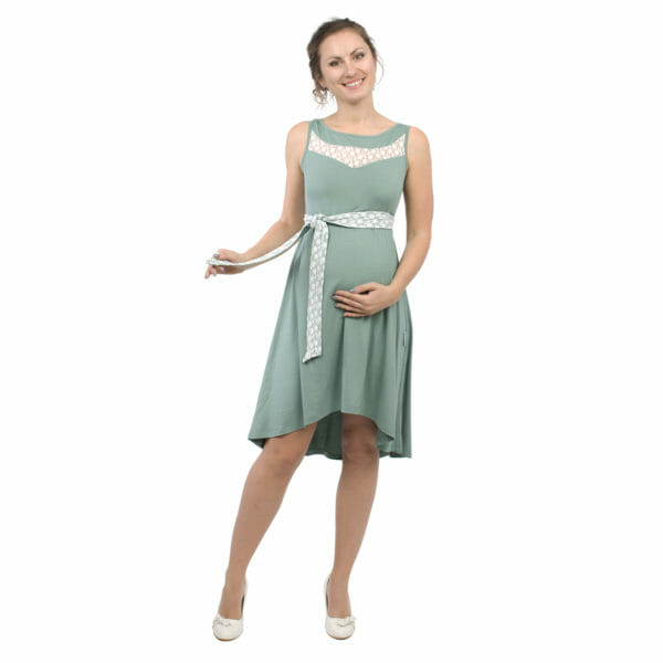 Maternity and nursing cocktail dress ALMA in mint with white lace - pregnant model with hand under baby bump and other hand holding belt - front view