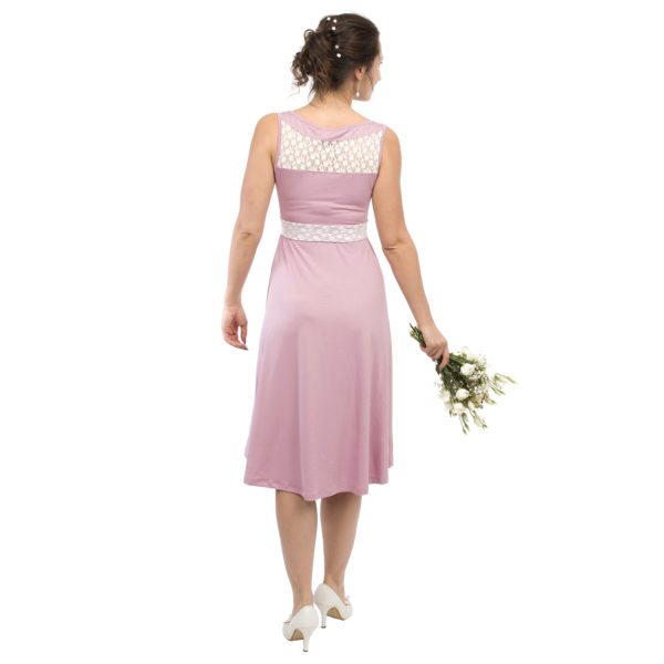 Maternity and nursing cocktail dress ALMA in pink with white lace - model wears dress and has bunch of flowers in right hand - view from back