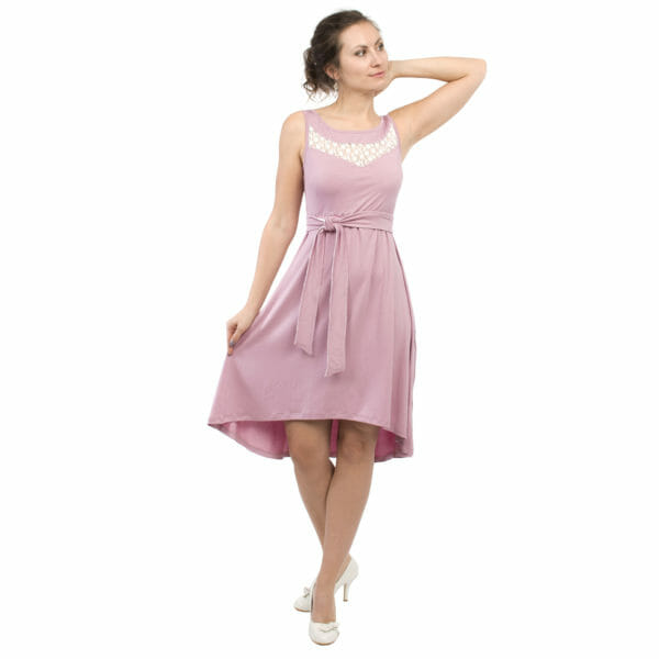 Maternity and nursing cocktail dress ALMA in pink with white lace - model wears dress with one arm behind head and holds skirt with other hand