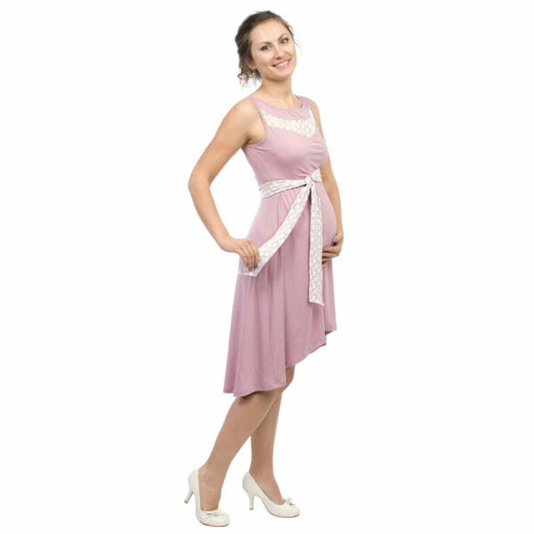 Maternity and nursing cocktail dress ALMA in pink with white lace - pregnant model with left hand under baby bump and right hand holding belt
