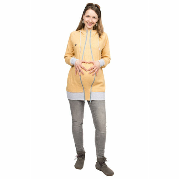 Babywearing Hoodie Summer Sweat CLEO in yellow - pregnant model wears jacket with pregnancy insert and forms heart with hands on baby bump - front view