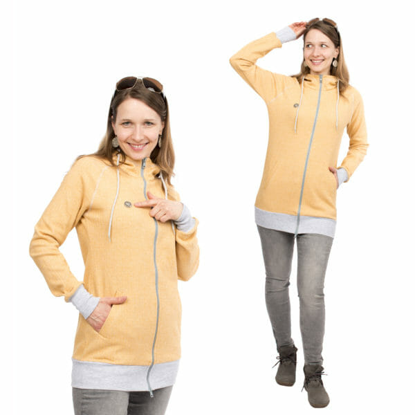 Babywearing Hoodie Summer Sweat CLEO in yellow - model wears jacket without inserts - on left hands side she points to the Viva la Mama metal heart logo on top right of jacket and on right hand side she has hand in pocket and other hand holds sun glasses on head