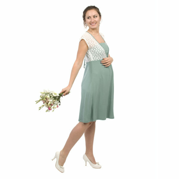 White lace top maternity and nursing dress JULIETTE in mint - pregnant model wears dress with bunch of flowers in her right hand and other hand on her baby bump - side view