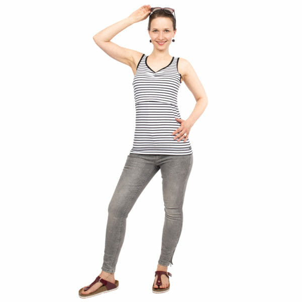 Maternity and nursing tank top SOLEA in black-white-stripes - model wears top with jeans and sunglasses on her head - front view