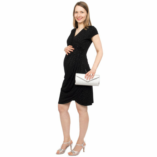 Festive maternity and nursing dress SAMSARA in black-silver - pregnant model wears dress with silver sandals and silver clutch and has hand on her baby bump - half side view