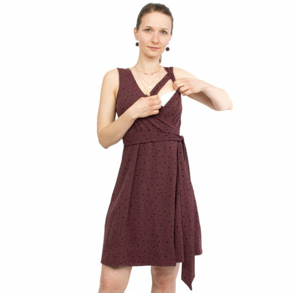 Maternity and nursing wrap dress TESSA in cassis with black dots - model wears dress and shows breastfeeding access