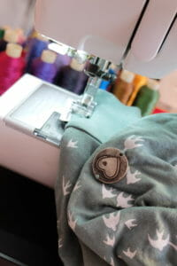 High quality standards at Viva la Mama and partners - shirt with Viva la Mama heart logo during sewing process