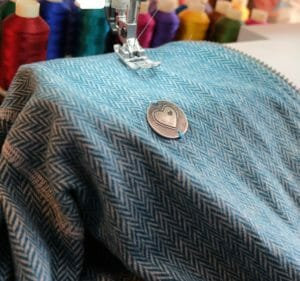 Jacket CLEO green lies under sewing machine for finishing touches