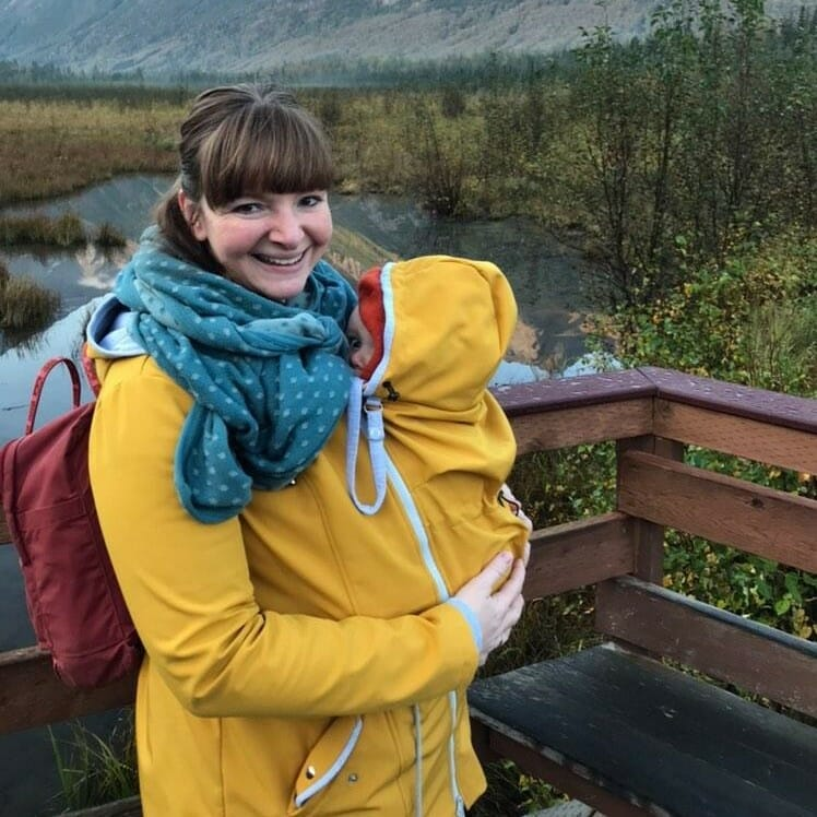 Customer Cati from Dortmund carries her baby in carrying jacket PINA mustard yellow