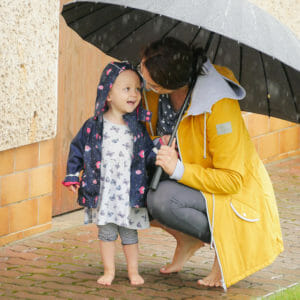 Softshell jackets are water resistant - Mum with toddler barefoot in summer rain