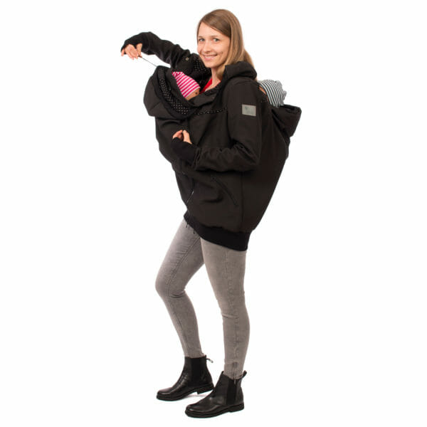 Twin baby carrier jacket TWINSTAR in black - babywearing moel wears jacket with insets front and back and adjusts baby's hood on front insert - side view