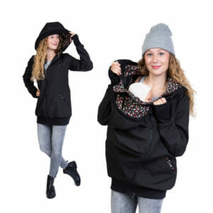 All-weather softshell babywearing jacket JACKY in black-scatter-flowers - model wears jacket - on the left without insert and hood on and on the right babywearing with carrying insert