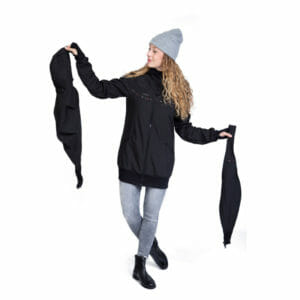 All-weather softshell babywearing jacket JACKY in black-scatter-flowers - model wears jacket and shows carrying insert on the left and pregnancy insert on the right